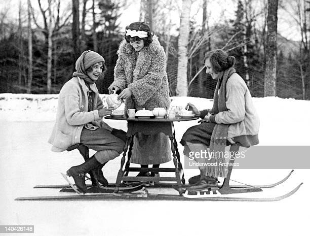 Two young women ice skaters at the Lake Placid Club enjoy an afternoon tea served hot off a tea table mounted on skir unners Lake Placid New York...