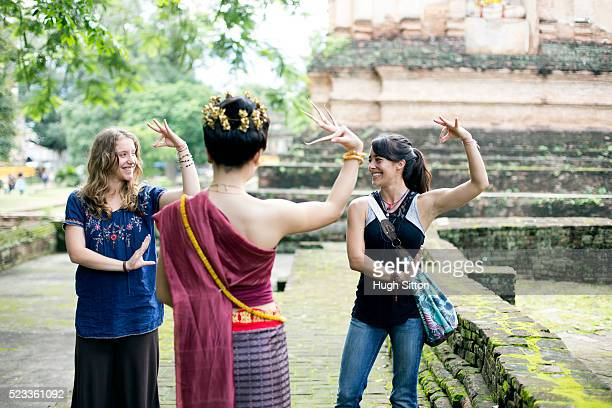 two young women imitating traditional thai dance, chiang mai, thailand - hugh sitton stock pictures, royalty-free photos & images