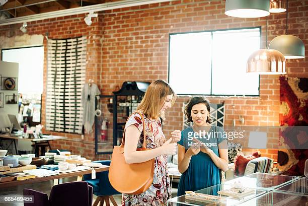 two young women in a shop, looking at jewellery. - jewellery products stock photos and pictures