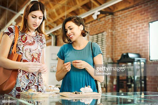 Two young women in a shop, looking at jewellery.