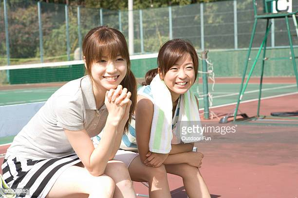 Two young women in a tennis court, resting