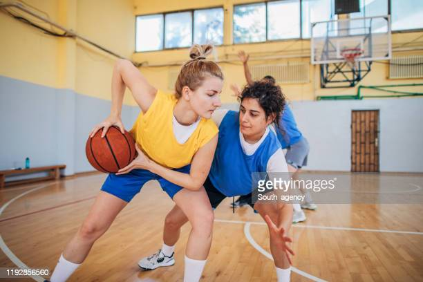 two young women in basketball duel - women's basketball stock pictures, royalty-free photos & images