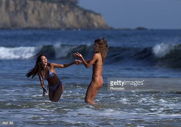 two young women in bikinis are playing in the ocean waves and splahing eachother