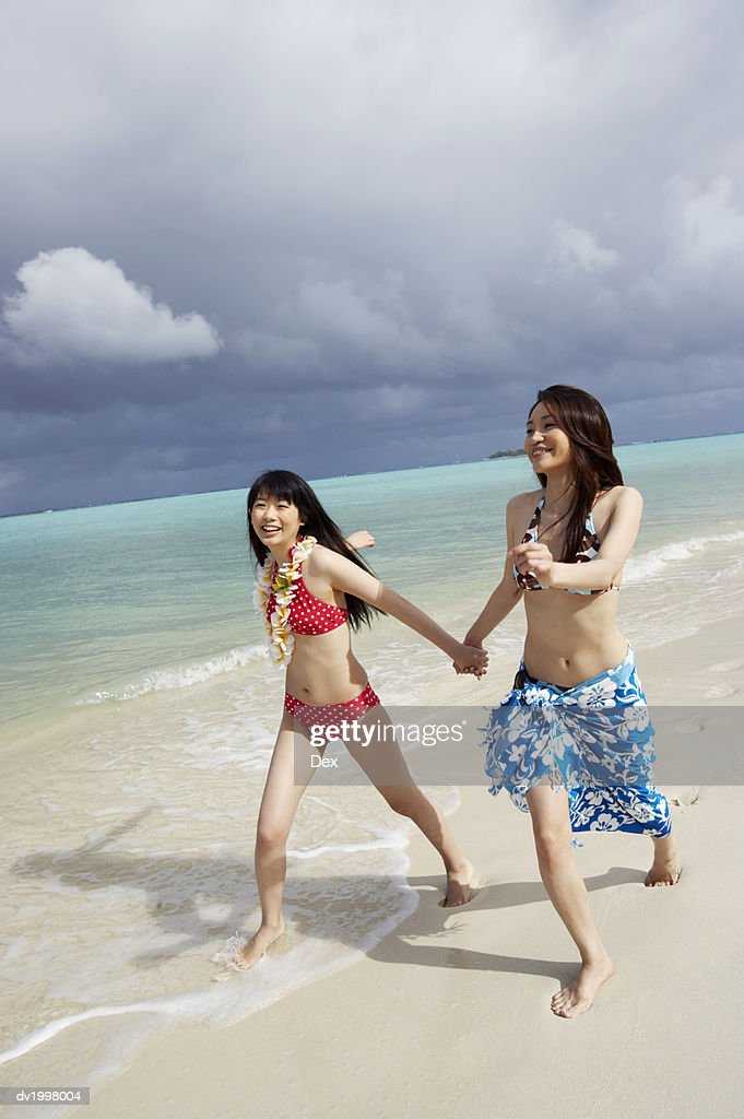 Two Young Women in Bikinis Walk Along the Beach Holding Hands : Stock Photo