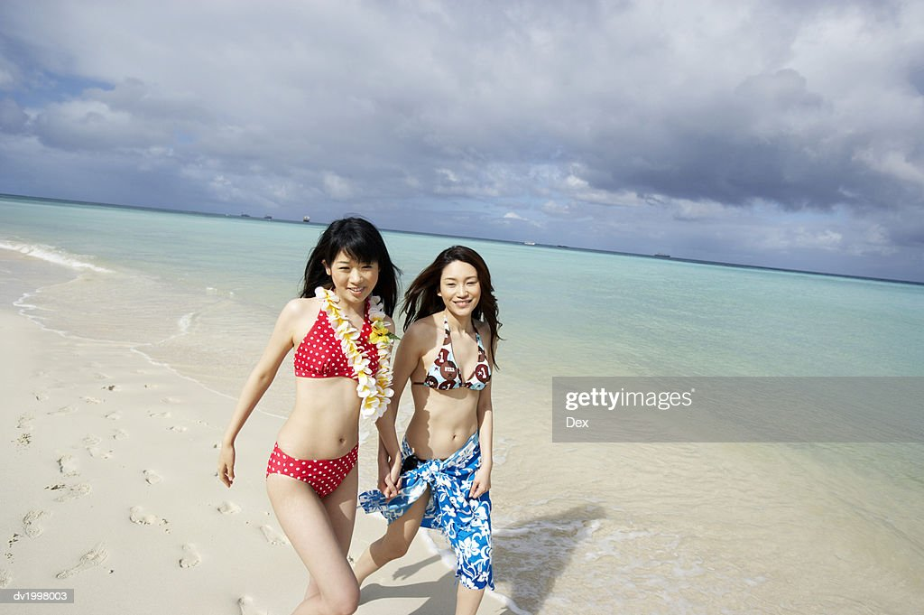 Two Young Women in Bikinis Walk on the Beach by the Water's Edge : Stock Photo