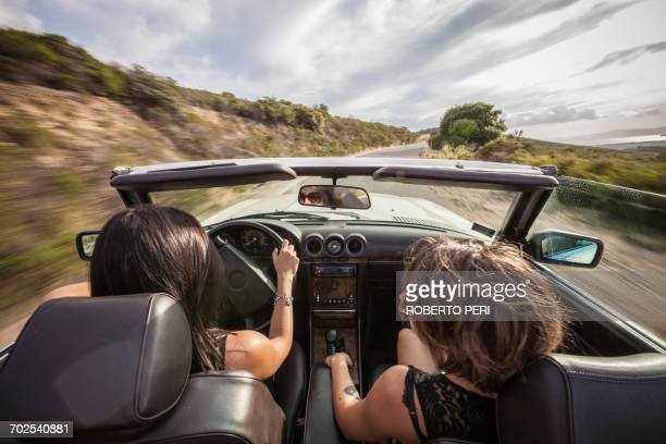 Two young women in convertible car, driving along scenic road, rear view