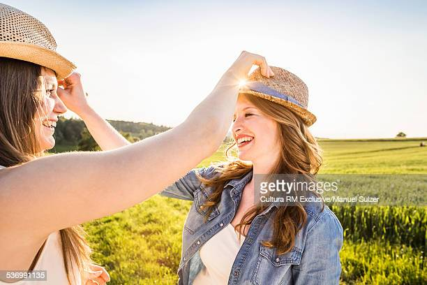 Two young women in field, switching hats