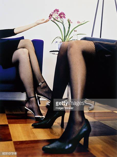 two young women in fishnet stockings sitting face to face - short skirts and stockings stock photos and pictures
