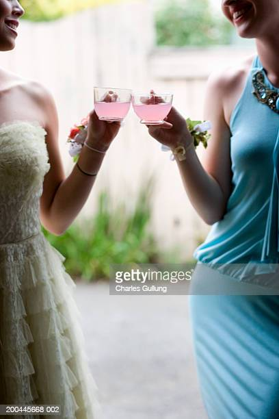 Two young women in formal dresses drinking juice, smiling, mid section