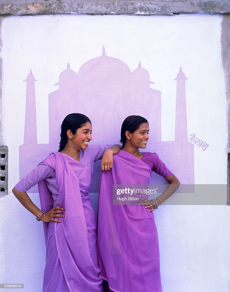 Two young women in front of mural painting of Taj Mahal wearing sari, India : Stock Photo