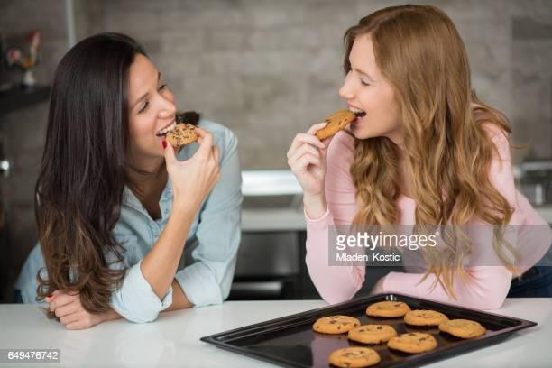 Dos mujeres jóvenes en cocina hornear galletas de chispas de chocolate