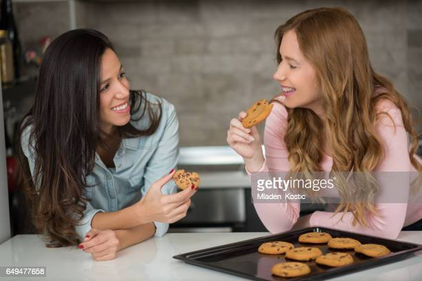 Two young women in kitchen baking chocolate chip cookies