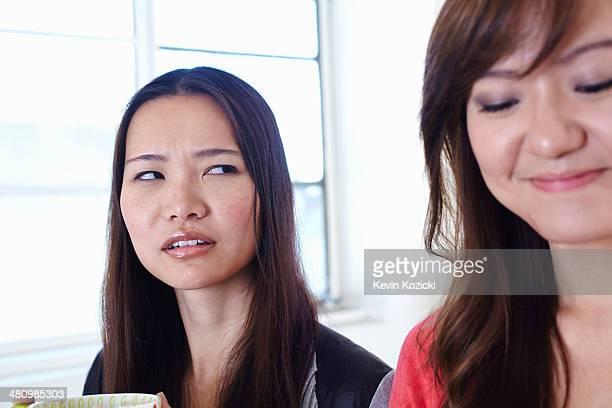 two young women in kitchen in disagreement - seitenblick stock-fotos und bilder