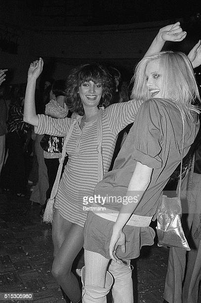 Two young women in mini dresses dance at Studio 54 in New York