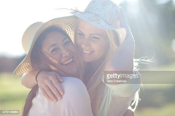 Two young women in park posing in sunhats