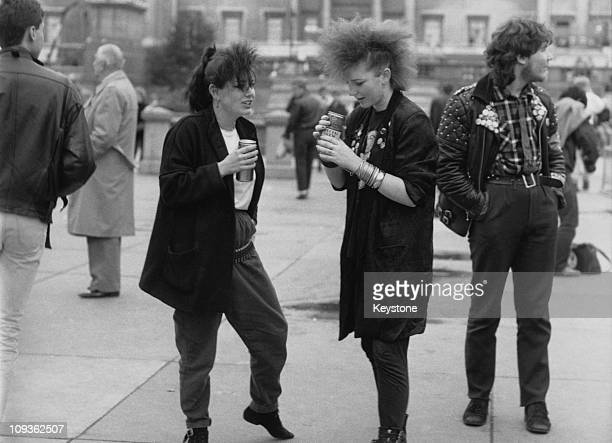 Two young women in postpunk fashions drinking beer from cans 1987