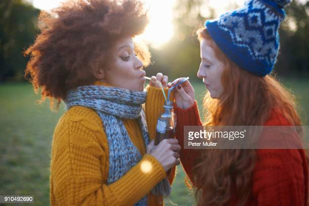 Two young women, in rural setting, drinking from bottle with straws