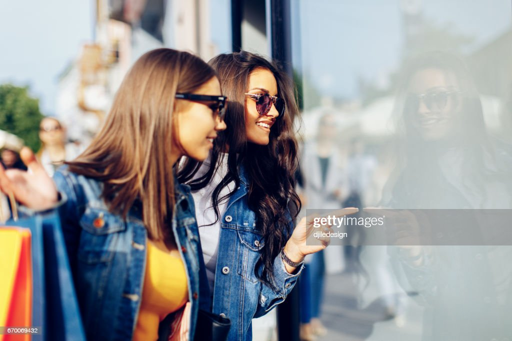 Two young women in shopping looking at shop window in the city : Stock Photo