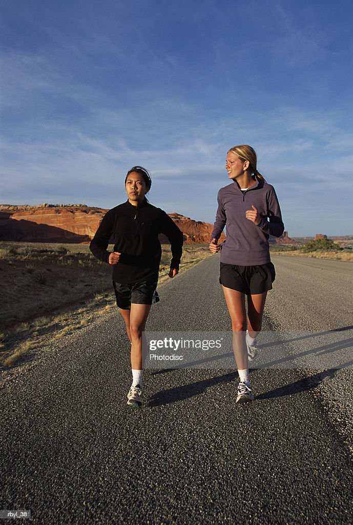 two young women in shorts and long sleeve shirts are running along a road in the south utah desert : Foto de stock