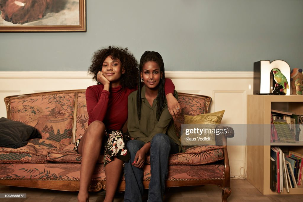 Two young women in sofa at home : Stock Photo