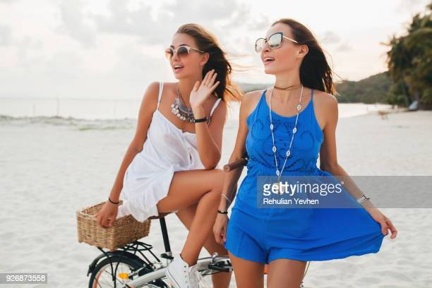 Two young women in sundresses with bicycle on sandy beach, Krabi, Thailand