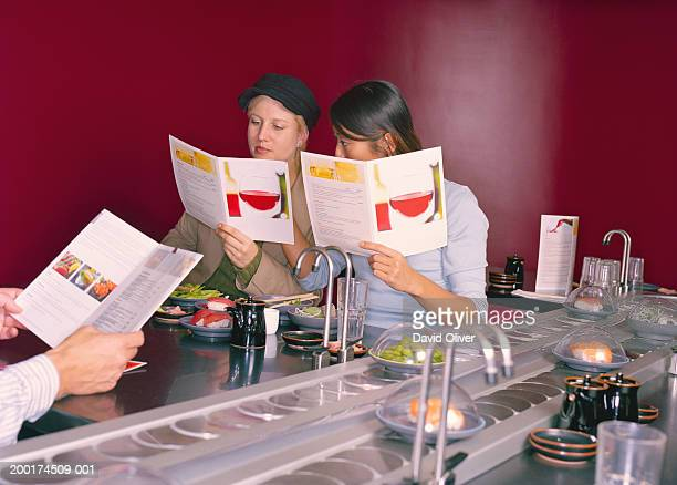 Two young women in sushi restaurant looking at menu