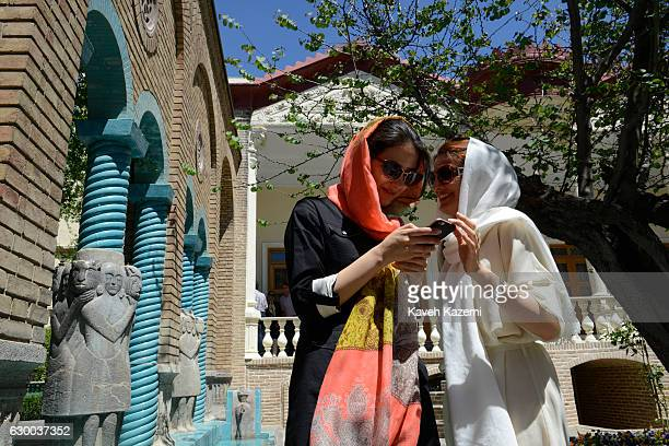 Two young women in veils look at a snap photo taken on a mobile device in the garden of Moghadam House on April 22 2016 in Tehran Iran Moghadam house...