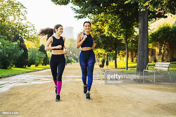 Two young women jogging in park