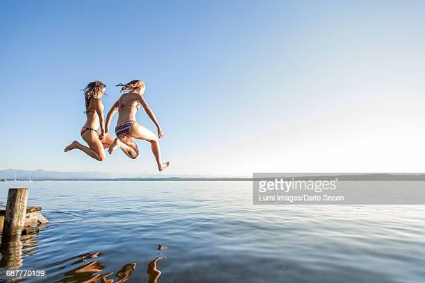 two young women jumping into lake - weibliche freundschaft stock-fotos und bilder