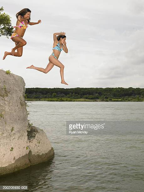 Two young women jumping off rock into lake, holding noses