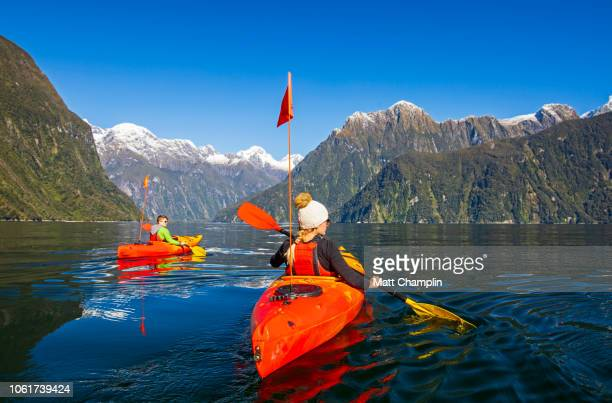 two young women kayaking in milford sound in new zealand - southland new zealand stock pictures, royalty-free photos & images