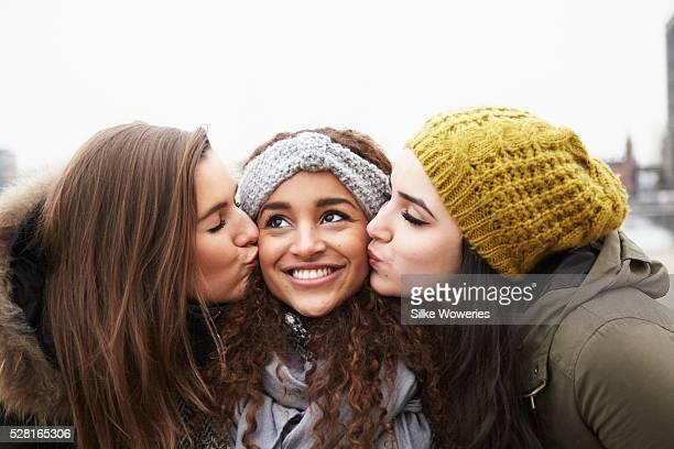 Two young women kissing friend,