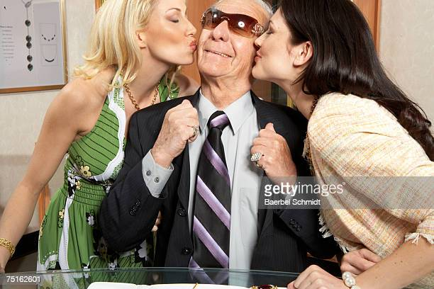 Two young women kissing senior man on cheek