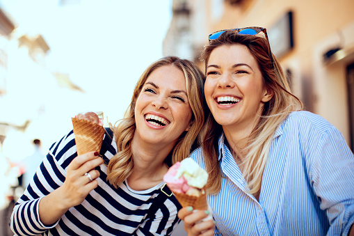 Two young women laughing and holding ice cream in hand 936618458