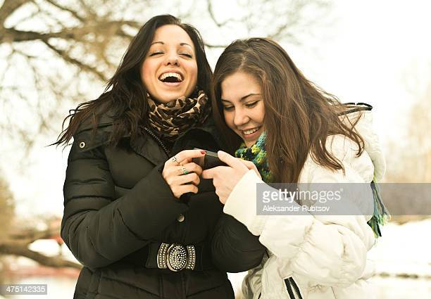 Two young women laughing at mobile phone in park in winter