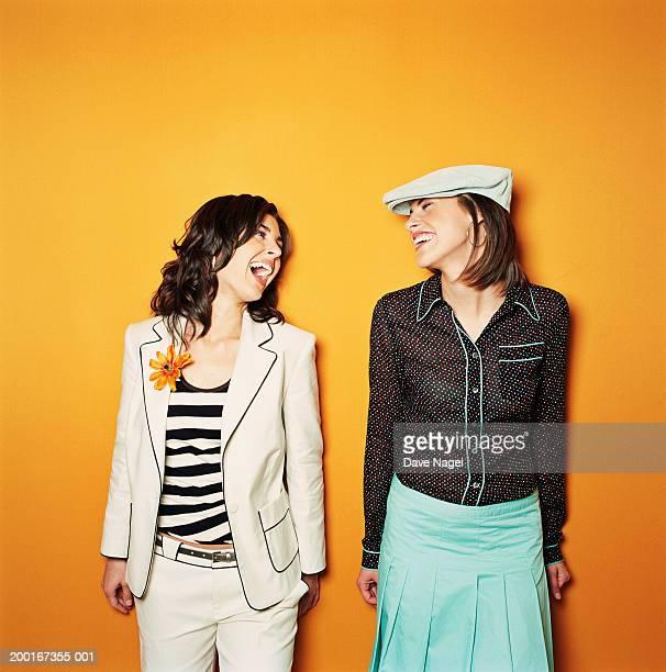 two young women laughing - côte à côte photos et images de collection