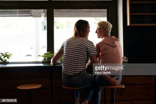 Two young women laughing together in café