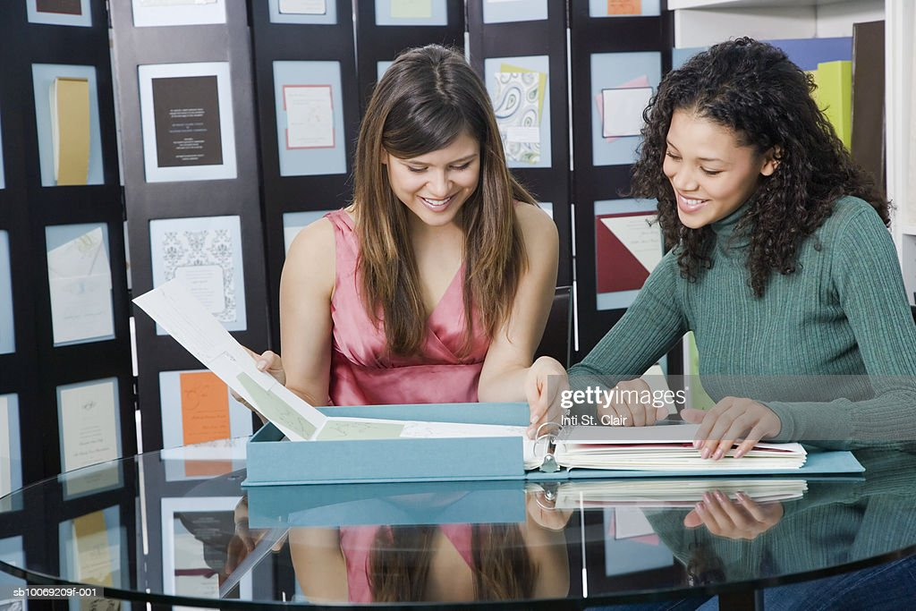 Two young women leafing through folder in shop : Stockfoto