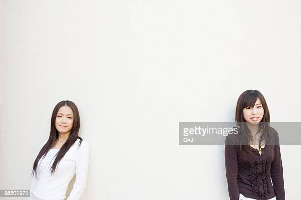 Two Young Women Leaning Against Wall, Copy Space