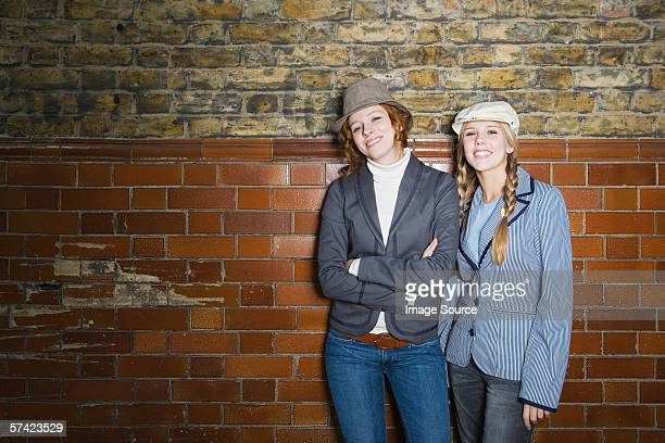 Two young women leaning against wall