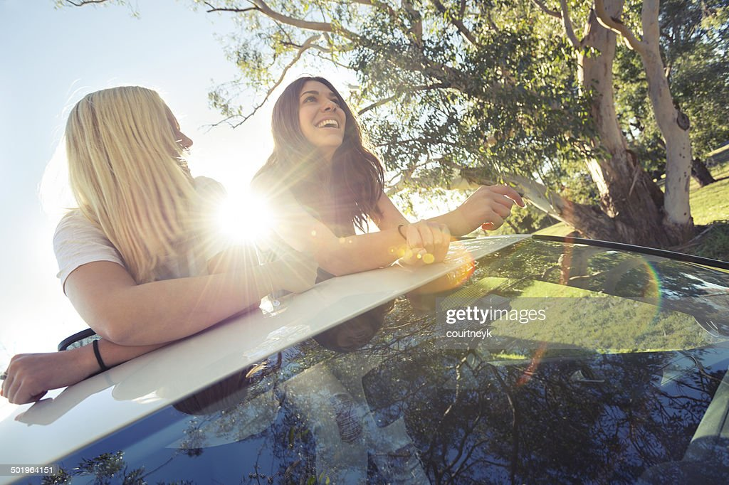 two young women leaning out of a sunroof backlight by the sun : Stock Photo
