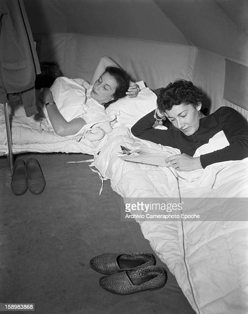 Two young women lie in their camp beds one asleep the other reads a newspaper Padova Italy 1950