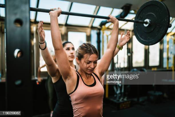 dos mujeres jóvenes levantando pesas en el gimnasio - parte del cuerpo humano fotos fotografías e imágenes de stock