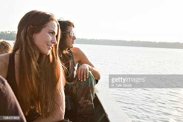 Two young women look into the sunset over Lake Sandoval, in the amazon rainforest.