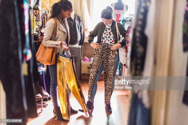 two young women looking at clothes in a vintage clothes shop - vintage fashion stock pictures, royalty-free photos & images