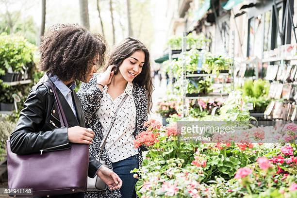 Two young women looking at flowers and smiling