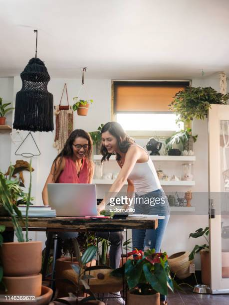 Two young women looking at laptop computer in workplace