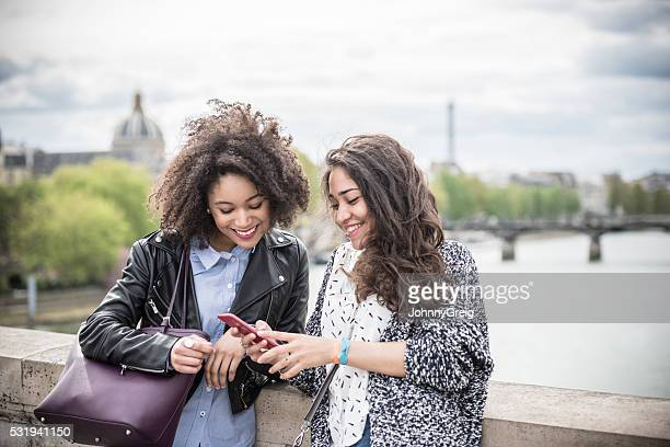 Two young women looking at mobile phone togteher