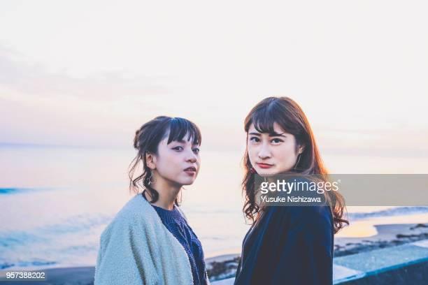 two young women looking at one point - yusuke nishizawa stock-fotos und bilder