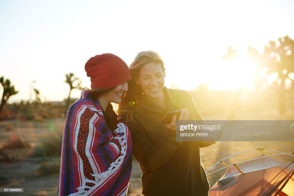 Two young women looking at phone at campsite : Stock Photo